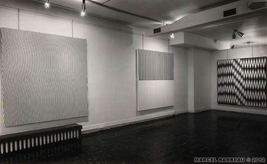 Exposition «Marcel Barbeau» à la East Hampton Gallery, New York, septembre 1965. À l'arrière plan, «Rétine Django», acrylique sur toile, 1965. Photo O. E. Nelson , pour Marcel Barbeau. Auteur : Nelson, O. E. Date : 09/11/1965